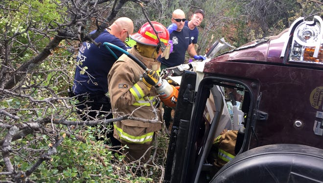 This photo provided by Kim Moore shows firefighters working to extricate a 50-year-old man from his crashed car on Mingus Mountain in Yavapai County, Arizona on Friday, May 27, 2016. Authorities say a man trapped in his crashed vehicle on a central Arizona mountain for three days was rescued thanks to a couple taking sightseeing photos