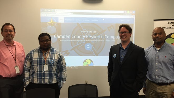 Hopeworks members Kevin Aspell (far left), Justin Connor (left), Dan Rhoton (right), and Preston Beckley (far right) pose in front of screen showcasing homepage to Compass website.