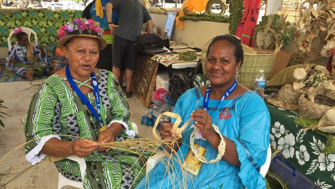 New Caledonia weavers Marie Malo and Wejieme Maria take a photo with their weavings at the Festival of Pacific Arts main village in Paseo on June 2.