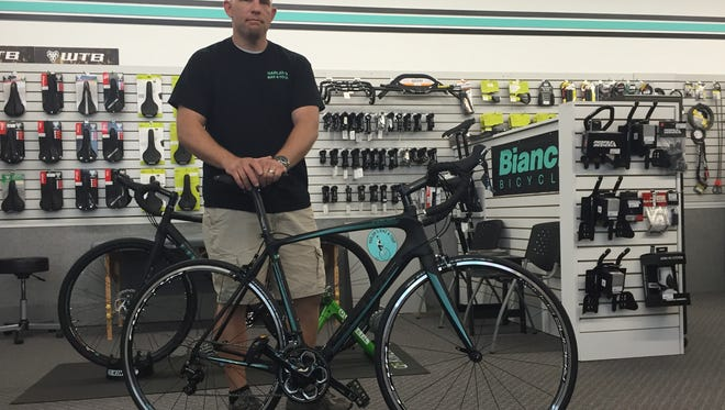 Chris McNally poses with his bike at the store he manages, Harlan's Bike & Tour. McNally took up cycling for exercise after his diabetes diagnosis.