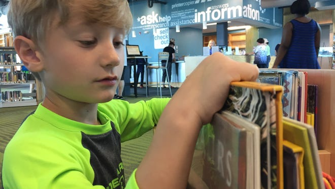 In this Saturday, June 4, 2016 photo, Max Davis, 6, browses books at the new Crisfield Library after a morning dedication of the structure. Max lives in Pocomoke City and visits the library in Crisfield during visits to his grandparents, Bonnie and George Milbert.