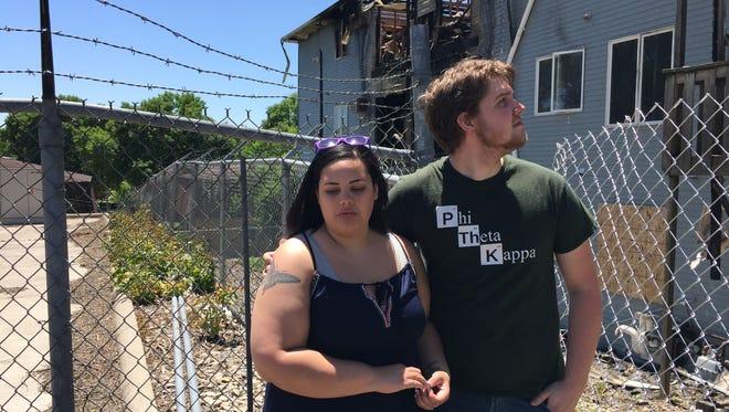 Abby and Matthew  Epperson, gaze at their apartment complex which caught fire on June 6. It rendered the couple homeless on the day of their honeymoon.
