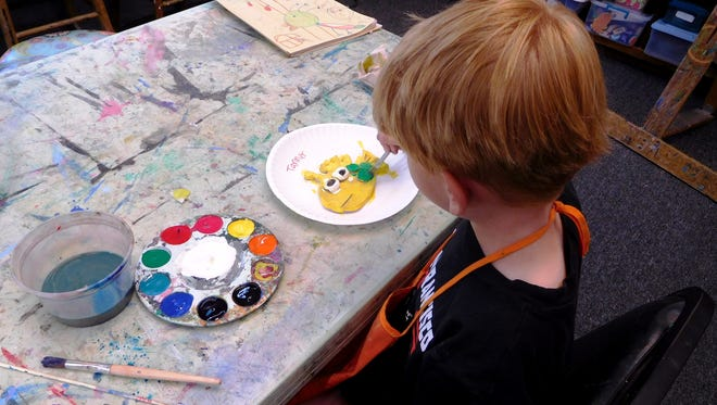 Tanner Hess adds details to his fish at Brush & Palette summer camp.