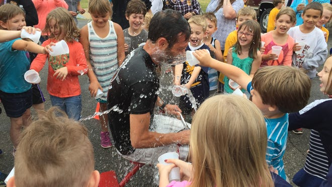 Algonac Community Schools Superintendent John Strycker gets splashed with water by kindergarten students at Millside Elementary on Thursday, June 16, 2016. Strycker enjoys developing rapport with students from an early age.