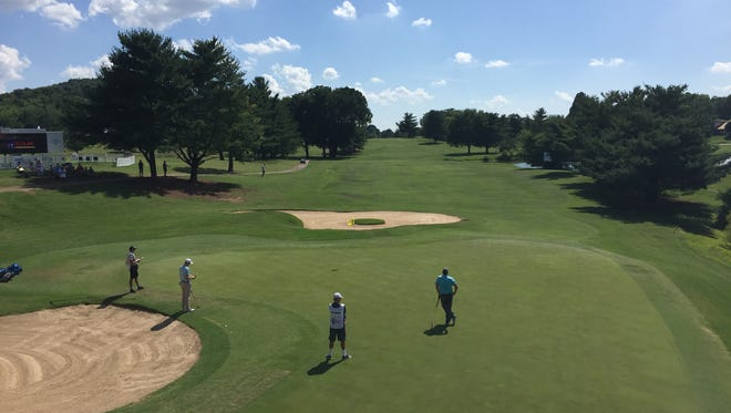 Players study the green on the18th hole at Nashville Golf & Athletic Club during Thursday's Nashville Golf Open.