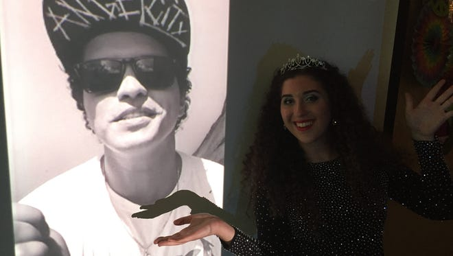 Fantastic Friends creator Marissa Hacker poses next to a photo of Bruno Mars. The pop star gave the special needs group a surprise video shoutout at their prom on Friday night.