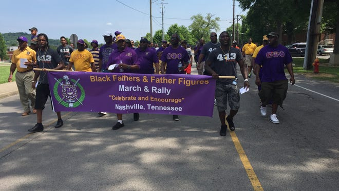 """Participants in The Black Fatherhood Celebration March+Rally pass the public housing complex known as """"Dodge City"""" to arrive at Metro Police's North Precinct on 26th Avenue North."""