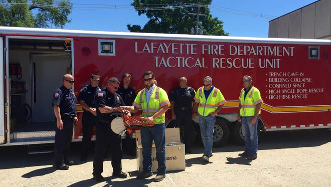 Joe Henrys of Walsh Construction presents Lafayette Fire Department Capt.  Randy Evans with a new Husqvarna ring saw.