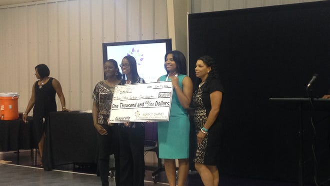 Dahia Jackson and Carol Houston stand with their mothers, Labrina Cannon-Merriweather, far left, and Latony Houston, far right, during a scholarship ceremony Saturday.