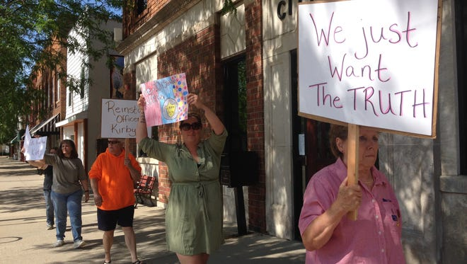 Supporters of fired police Officer Lisa Kirby picket June 13 in front of Eaton Rapids City Hall.