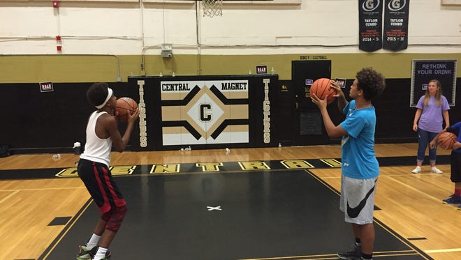 Davone McCullough, left, and Anthony Bullard practice at Reaching Our Athletes Responsibly basketball camp.