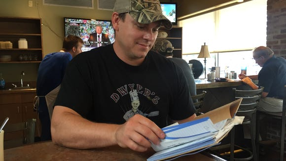 Dwyer's Cafe co-owner Brett Dwyer flips through a book of memories his mother, Debbie Dwyer, started. A few of the memories in the book pay tribute to Loula Mae Landry, a longtime waitress who died Monday.