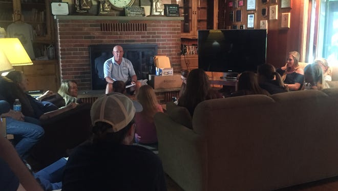 Howard Stuart talks to his team Wednesday at his home, as they celebrate Richmond High School's first softball title