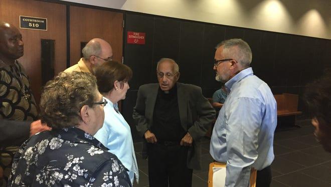 Rev. Timothy Kane, on right, speaks to Rev. Norm Thomas and other supporters in Wayne County Circuit Court on June 30, 2016.