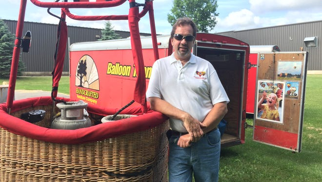 Steve Woller stands with one of his baskets, which holds four people.