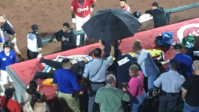 A woman, whose feet are visible at right, is treated after being struck by a bat during the Chihuahuas game Friday night in Southwest University Park.