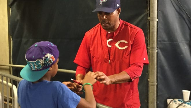 Cincinnati Reds Hall of Fame shortstop Barry Larkin signs a ball for a young fan following Saturday night's Blue Wahoos game.
