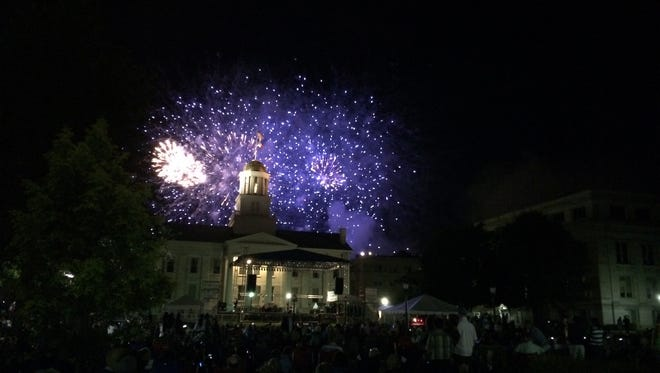 Fireworks burst behind the Old Capitol in downtown Iowa City as crowds watch from the Pentacrest lawn on Sunday evening, part of the city's Jazz Fest and July Fourth celebration.