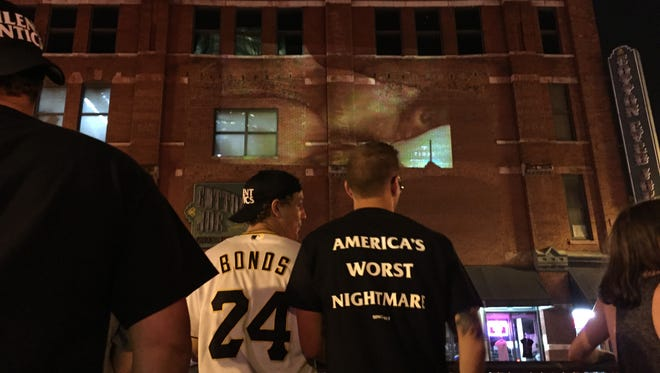 Fans gather on Broadway to watch the video.