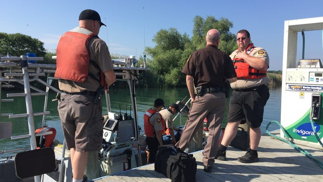 St. Clair County Sheriff Tim Donnellon speaks with members of the dive team before the search for a missing swimmer resumed Tuesday morning.