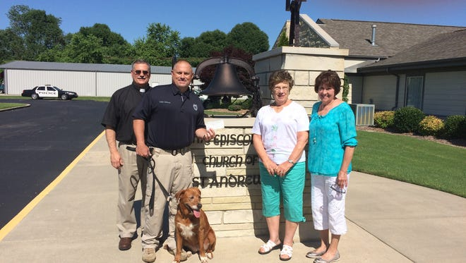 The Rev. Jim McDonald and the Women of St. Andrew's present a check for $500 to the School Resource Officer Canine Program. Shown are Rev. Jim McDonald, from left, Officer Eddie Helmert, Bomber, Jo Cushing and Deanna Van Eps.