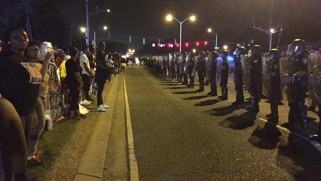 Protesters and police face off during demonstrations Saturday night in Baton Rouge.