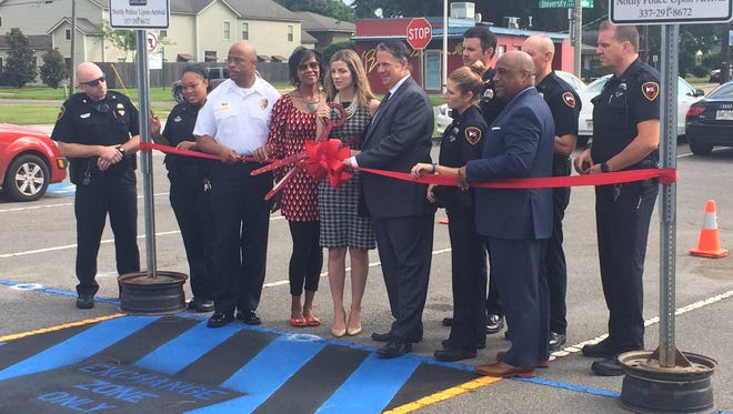 Lafayette Police and LCG representatives cut the ribbon on a dedicated parking spot for online exchanges.