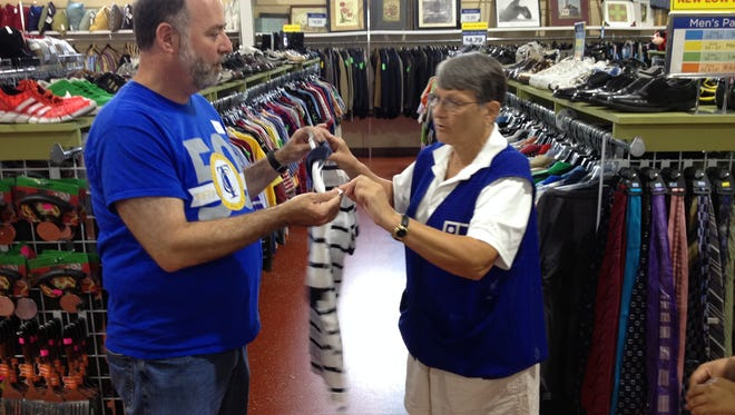 Bret Ingerman, vice president for information technology at TCC, left, gets instructions on retail display from Glenda Bevis Hebert Wednesday at Goodwill Industries on West Pensacola Street.