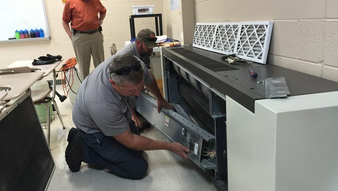 Maintenance Supervisor Bill Partin, left, watches as HVAC mechanic Tim Filson, right, and Norman Brake, a HVAC technician, disassemble a heating and air conditioning unit at Stewart County Middle School to replace filters and general maintenance.