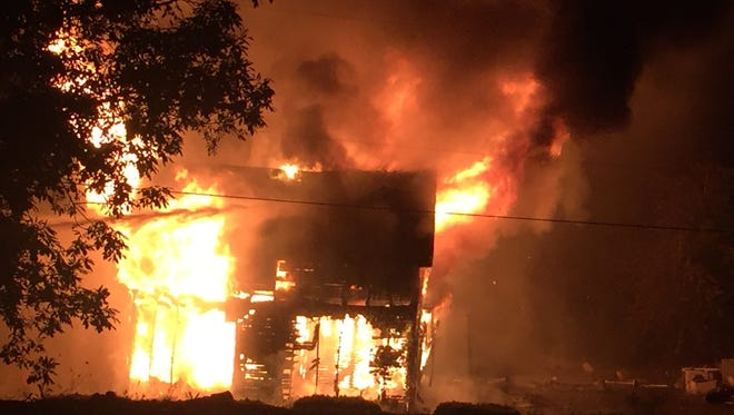 Flames engulf a two-story home in Falls City early Friday morning.