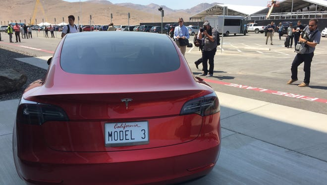 Photographers scramble Tuesday, July 26, 2016 to shoot a Tesla Model 3 during a tour of the company's battery Gigafactory east of Reno.