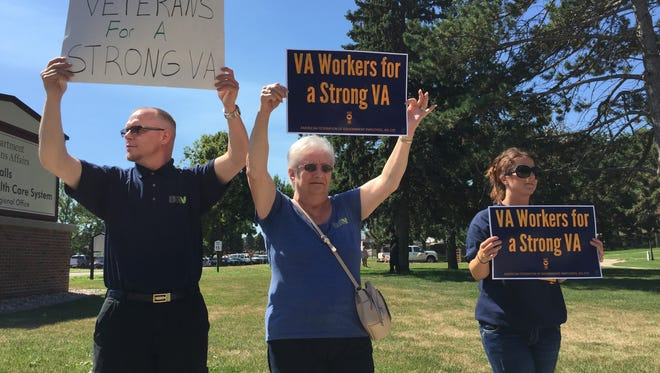 Protesters with the American Federation of Government Employees hold signs for passing cars on 22nd Street in Sioux Falls on July 26, 2016. The protesters are opposed to proposals to integrate the VA Health System with private providers.