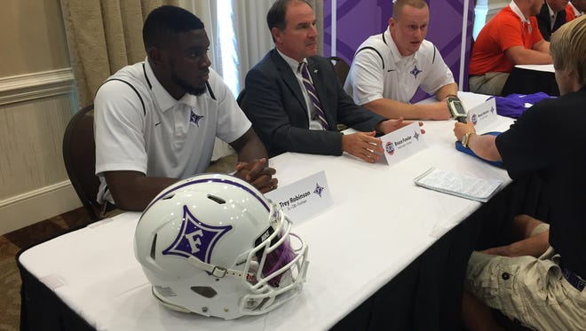 Furman safety Trey Robinson, left, coach Bruce Fowler, and quarterback Reese Hannon field questions at SoCon Media Day at the Spartanburg Marriott Wednesday.