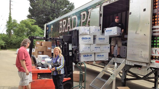 Richards & Southern logistics manager Bill Rippeto and President Sheri Calonge stand in front of a Brad Paisley bus that's being  loaded with merchandise.