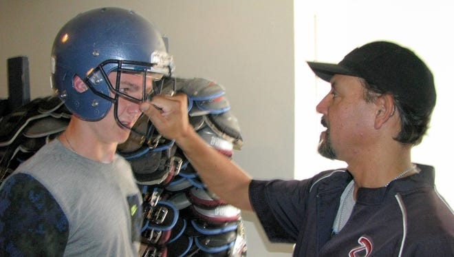 Sophomore Jaden Ruttle gets fitted for a brand new Wildcat helmet on Friday during equipment handouts at the Deming High School Memorial Stadium field house. DHS assistant coach Oscar Jurado makes sure Ruttle's helmet in a perfect fit. The Wildcats began two-a-day practices at 6 a.m. Monday, Aug. 1, 2016 at the DHS Practice Field.