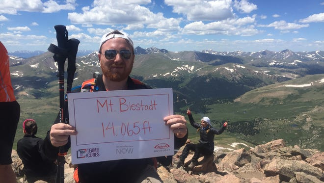 MItchell Happeney plans to climb Mt. Kilimanjaro in Africa next year to raise money and awareness of multiple myeloma, the disease his father suffers from. He climbed Mt. Bierstadt in Colorado last month to prepare.