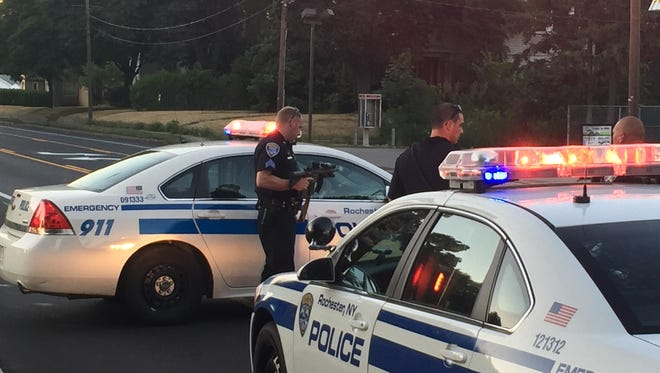 Rochester police officers help Irondequoit police shut down a portion of Hudson Avenue Tuesday for a shots fired investigation.