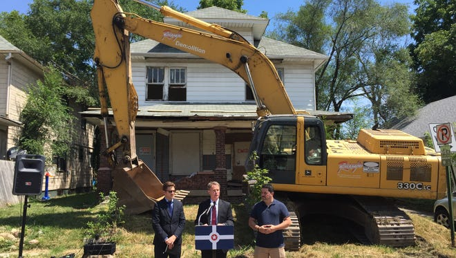 Indianapolis Mayor Joe Hogsett announces that the city has now torn down 99 homes using federal Hardest Hit funds. City-County Council Vice President Zach Adamson (right) and Jeff Bennett, deputy mayor of community development (left), joined him at a news conference at 253 N. Oxford St., which was demolished Monday, Aug. 8, 2016.