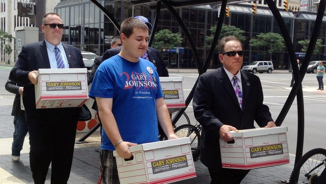 Libertarian Party activists in Ohio carry boxes of signature petitions to the Secretary of State's Office on Tuesday in Columbus, in hopes of placing presidential candidate Gary Johnson on the November ballot. The party surprised state election officials by submitting signatures for a different candidate, Charlie Earl, who ran unsuccessfully for governor in 2014,  in a move Libertarians defended as a placeholder effort because they began collecting signatures before Johnson was nominated. Once certified by the state's elections chief, Libertarians will swap in Johnson and his running mate.