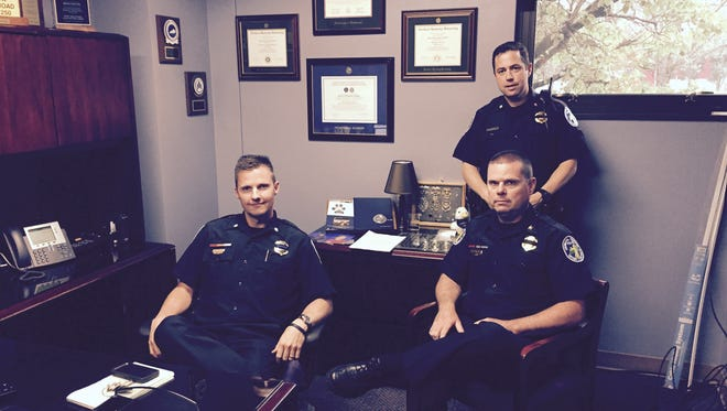 Covington Police Chief Bryan Carter (seated, right) with assistant chiefs Brian Steffen (left) and Robert Nader (standing).