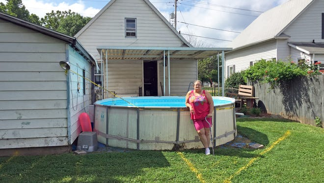 Veronica Goltz stands in her back yard near the Iowa State Fairgrounds that soon will be filled with parked cars.