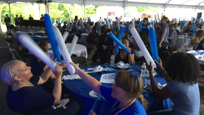 Wyndham Worldwide employees wave thundersticks during a pep rally to celebrate the company's 10th anniversary at its world headquarters in Parsippany on aug. 10, 2016.
