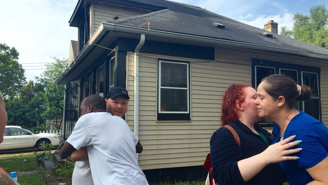 Dudley Carter, far left, and Stephanie Ross, far right, alerted their neighbors to a house fire in Lansing on Friday, August 12, 2016.