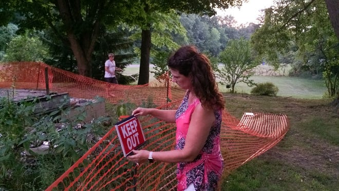 """Unadilla Township Trustee Susan Cox straightens a sign telling people to """"Keep Out"""" of the remains of her sons' burned down house. Son Adam Cox adjusts an orange snow fence around the site of the 2013 fire."""