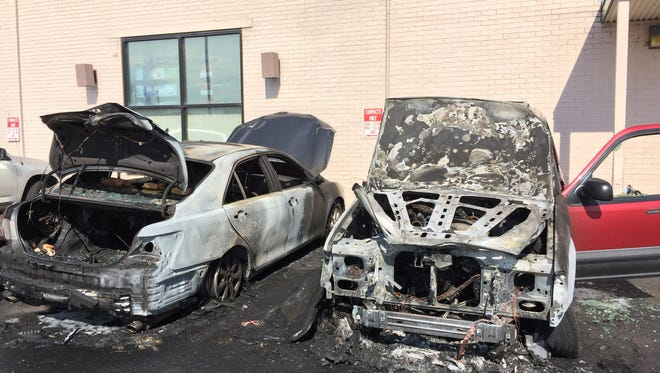 A blaze engulfed two unoccupied cars parked in the lot behind Wilbur's Total Beverage and forced a short evacuation of the building Sunday.