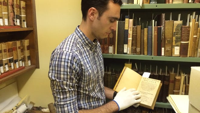 Ben DiBiase, archivist at the Library of Florida History in Cocoa, holds an original, Spanish language, first edition copy of a 1605 book about Hernando de Soto in Florida.