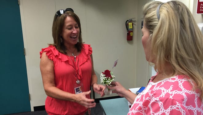 Cindy Mehok, a6th grade teacher at Pinewood Elementary, left, receives a rose from Dawn Acklin