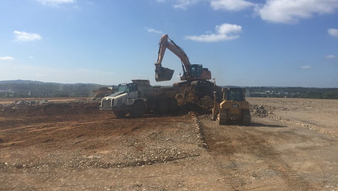 Workers move rocks at the summit of the West Manchester Township property that will become the new site of Memorial Hospital. About 30 vertical feet of ground has been removed, said project manager Jason Owens. Now workers are leveling that surface and moving debris.