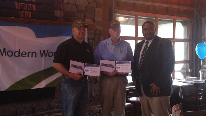"""Jackson Police Chief Julian Wiser, left, Madison County Sheriff John Mehr, middle, and Modern Woodmen representative Dekontee Sinclair pose for photos at Logan's Roadhouse Thursday night. Wiser and Mehr were recognized as the program's """"hometown heroes."""""""