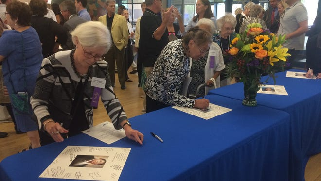 Guests sign photos for four newly-inducted members of the Iowa Women's Hall of Fame during a reception following the ceremony Saturday, Aug. 20, 2016 at the State Historical Building of Iowa.